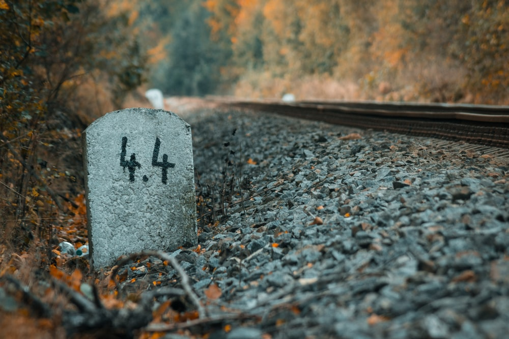 gray concrete tombstone near train rail