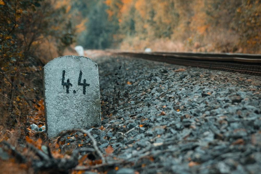 gray concrete tombstone near train rail