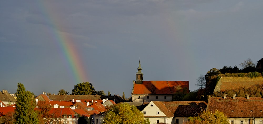 rainbow over houses during daytime