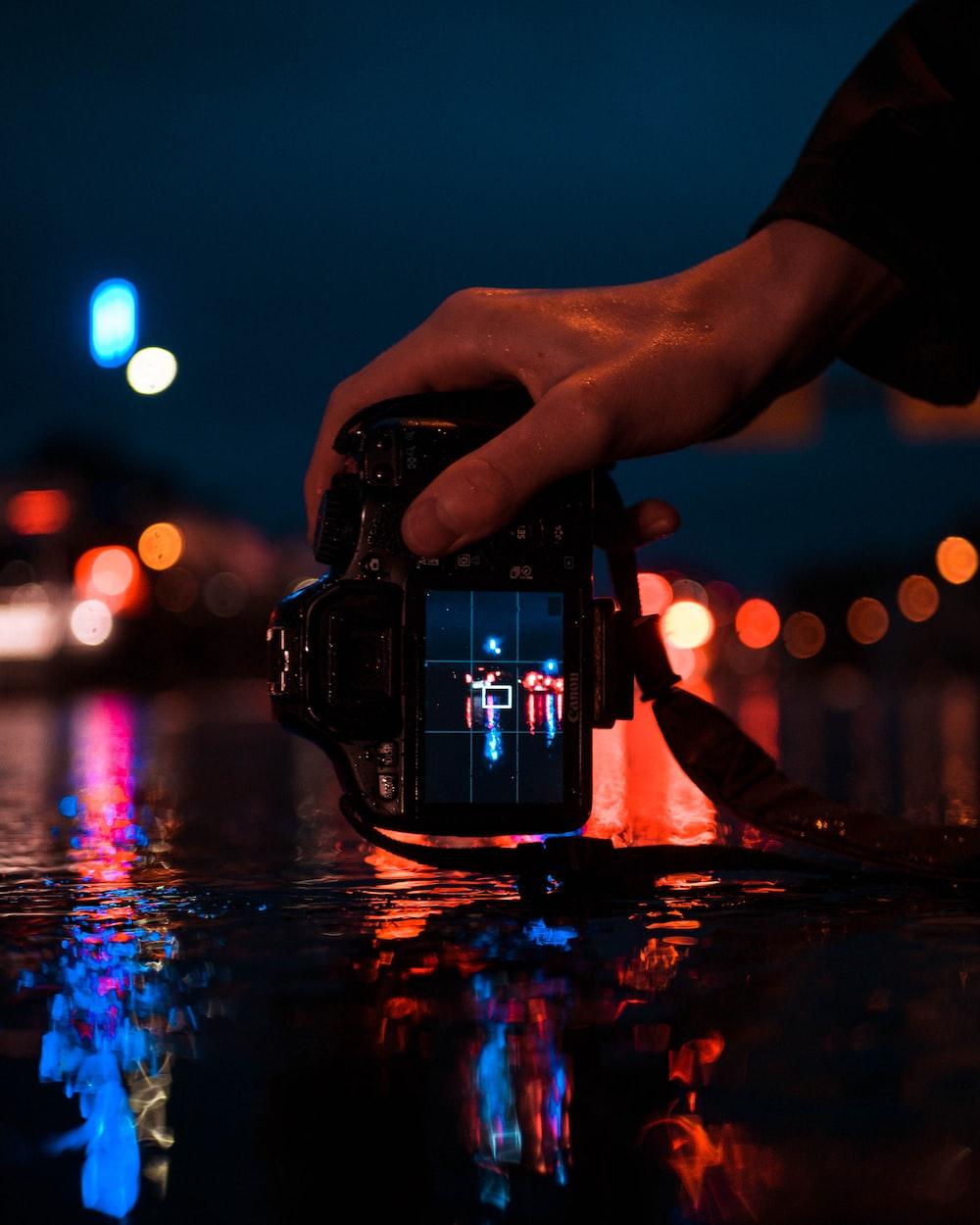person holding black DSLR camera taking photo of LED lights