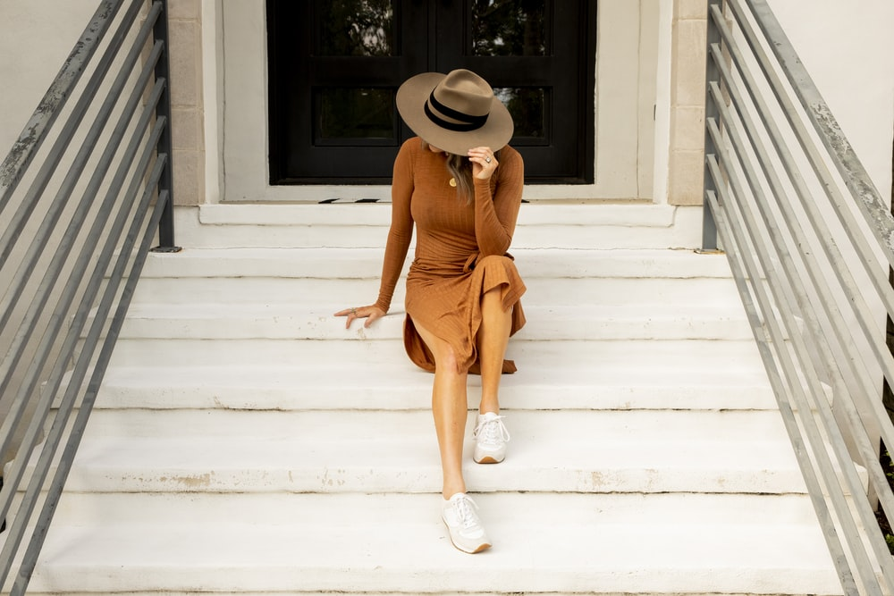 woman in brown dress wearing sun hat while sitting on stare during daytime