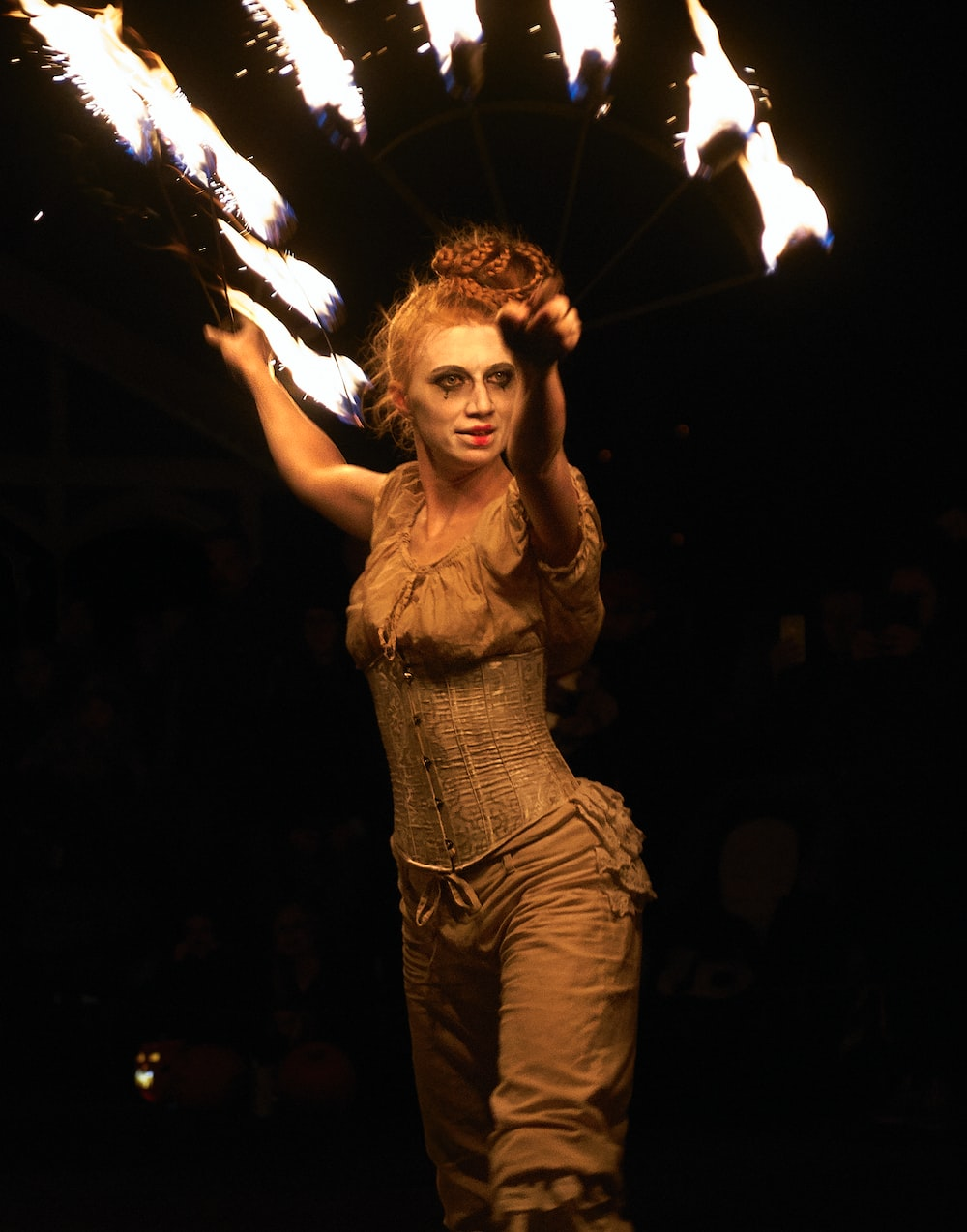 woman in costume holding stick with fire