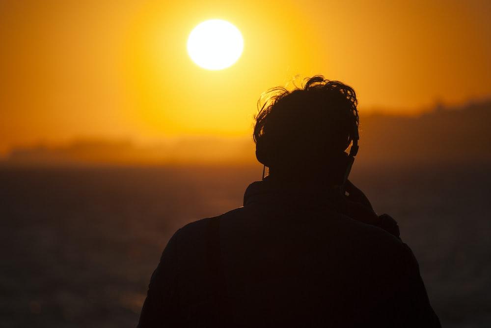 silhouette of man watching sunset