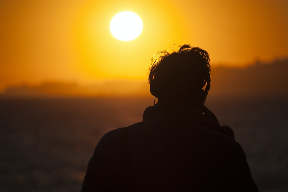 silhouette of man watching sunset