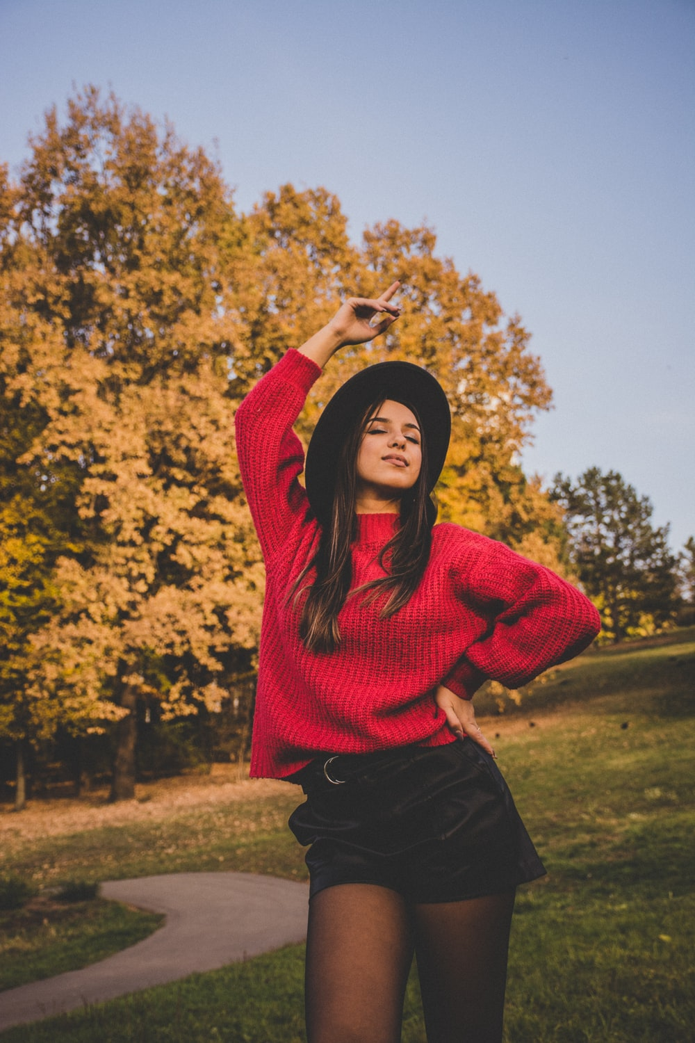 woman in red sweater standing on grass near trees during daytime