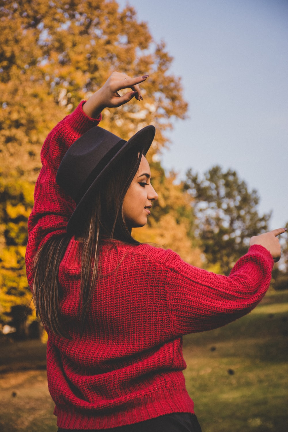 woman raising her hands while wearing red sweater and black fedora hat