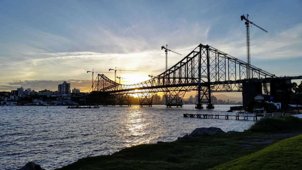 silhouette of bridge over body of water during golden hour
