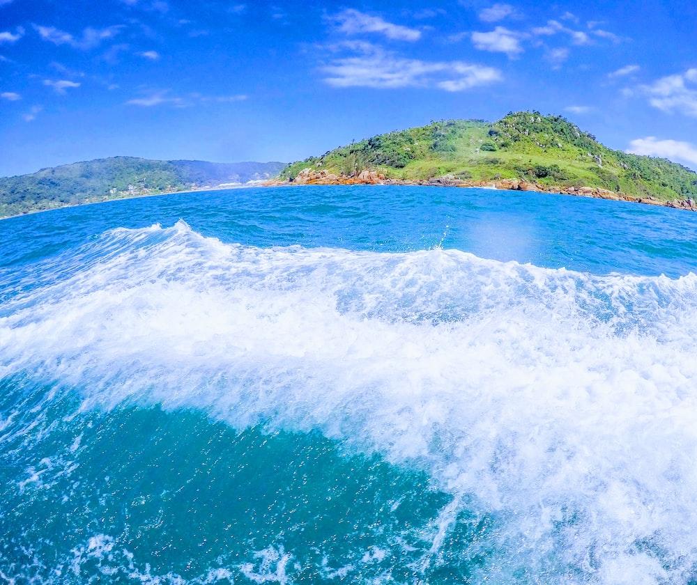 green mountain near body of water under blue sky