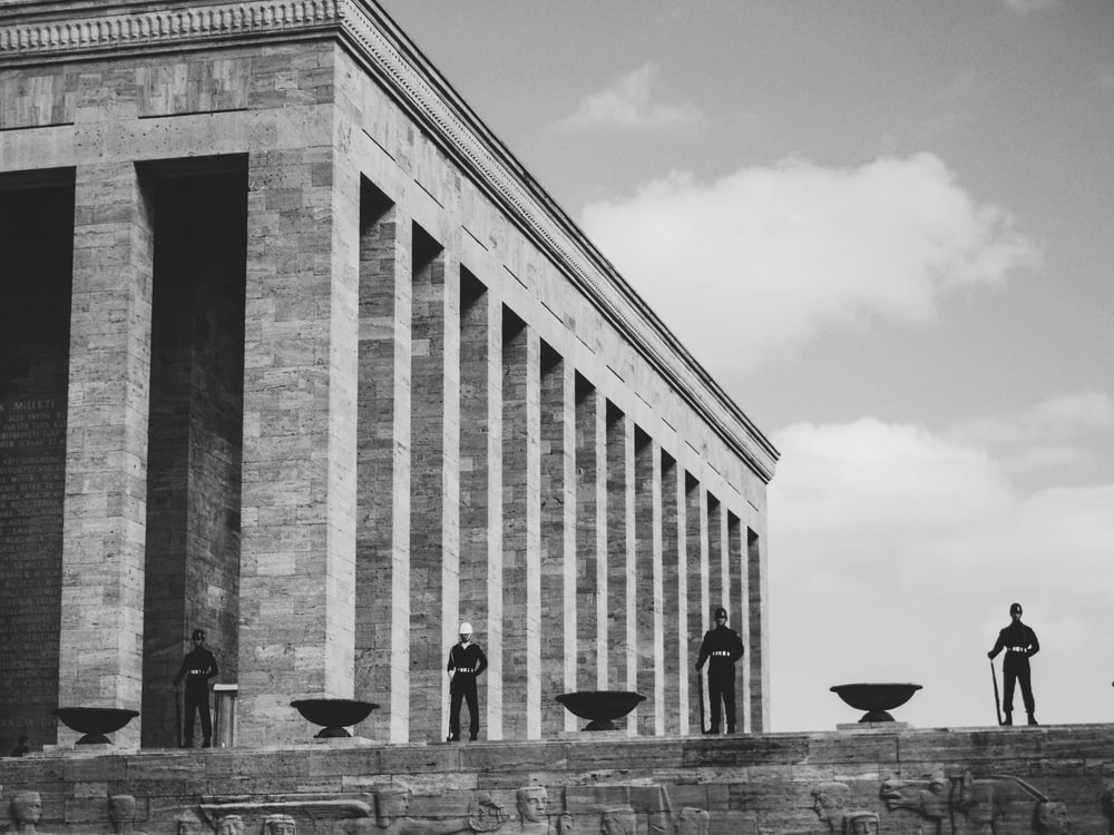 grayscale photo of men standing on hill near brick coliseum