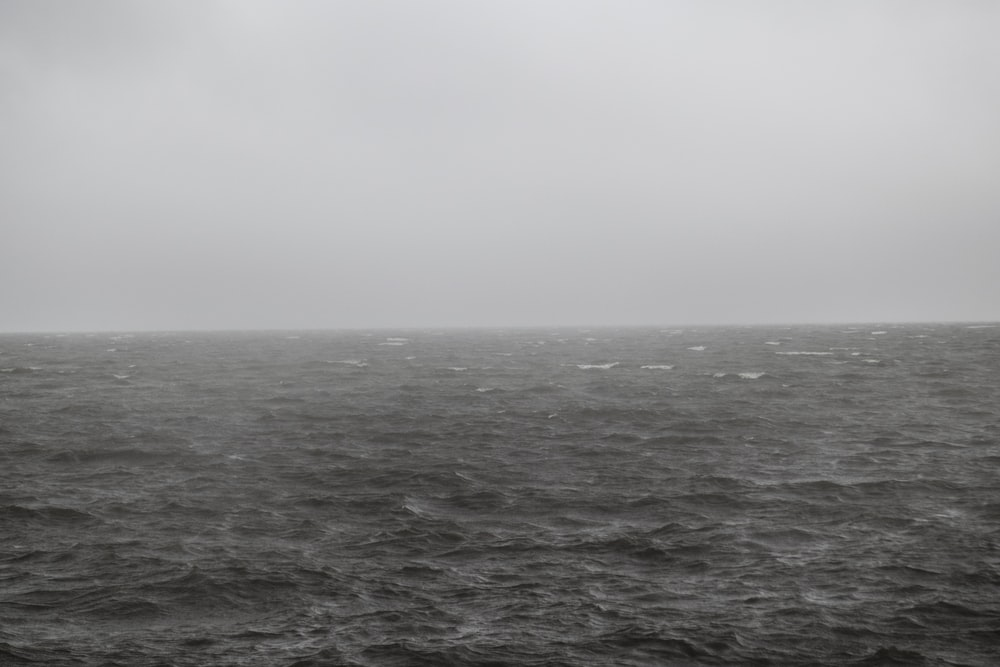 grayscale photo of waves on sea