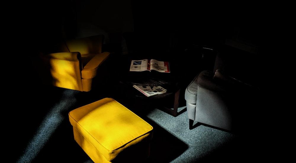 yellow ottoman inside dark room