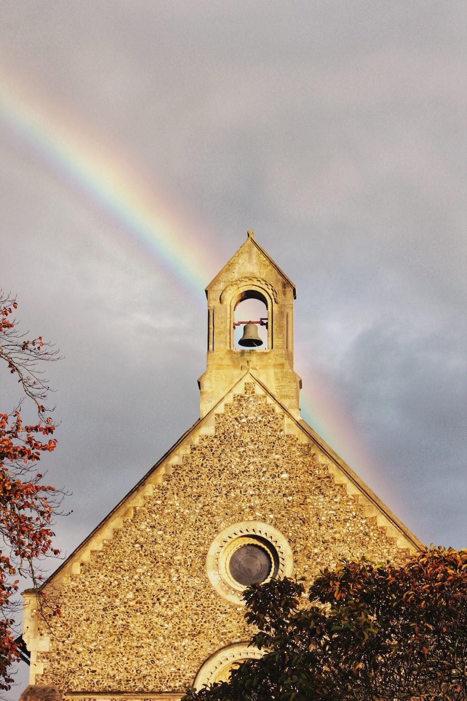 brown church under rainbow