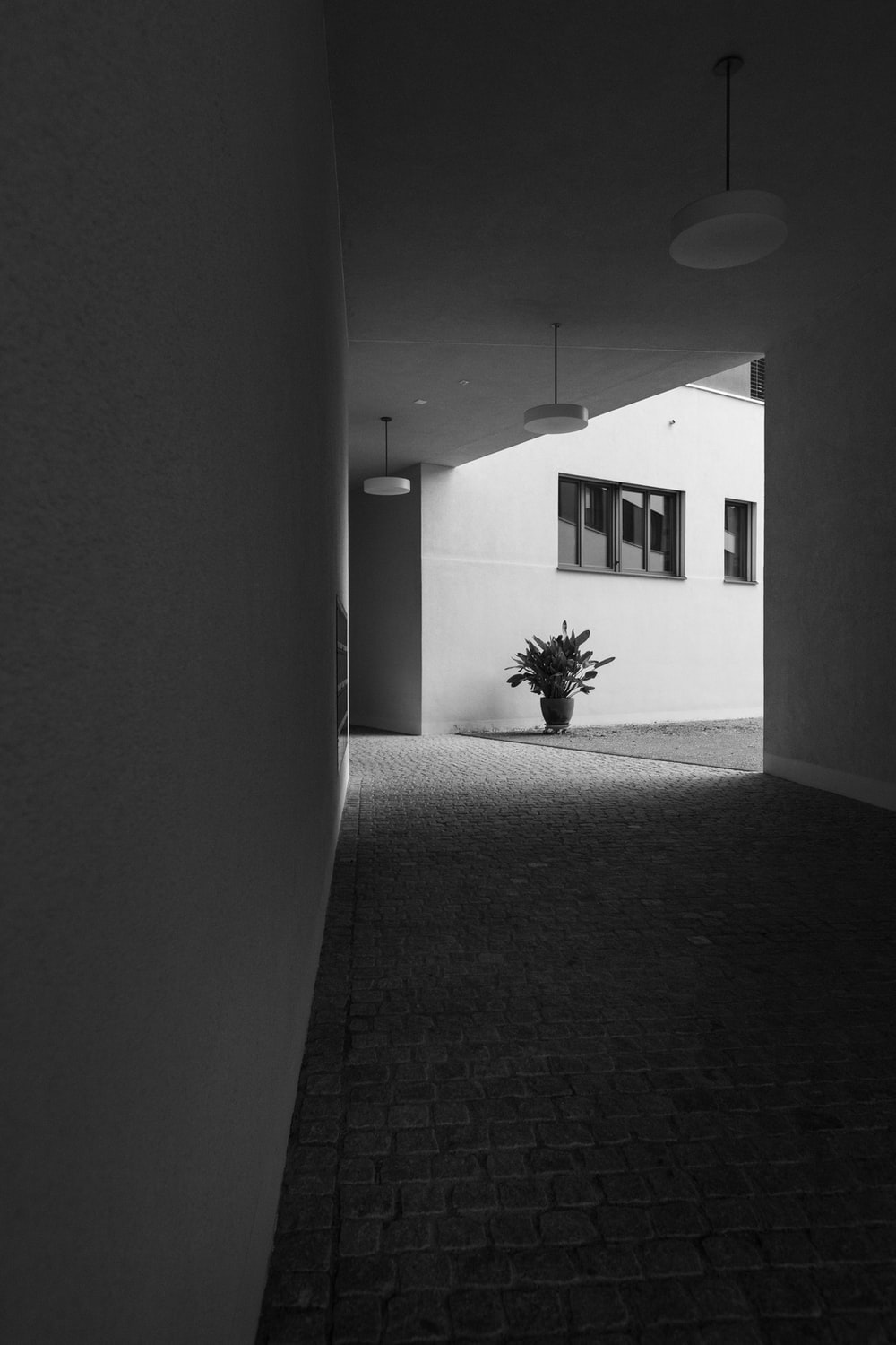 grayscale photo of hallway in room with pendant lamp