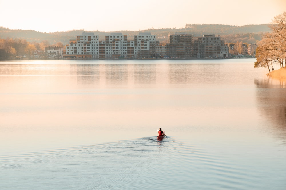 man riding on boat on calm body of water