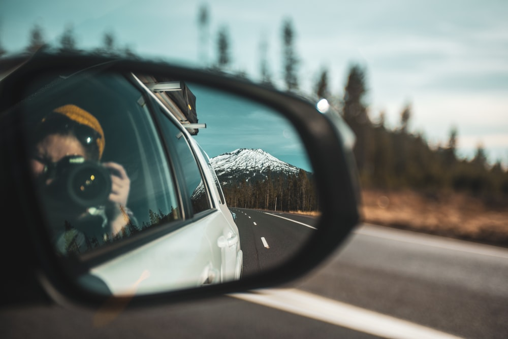 close-up photography of woman taking photo of mountain through vehicle side mirror