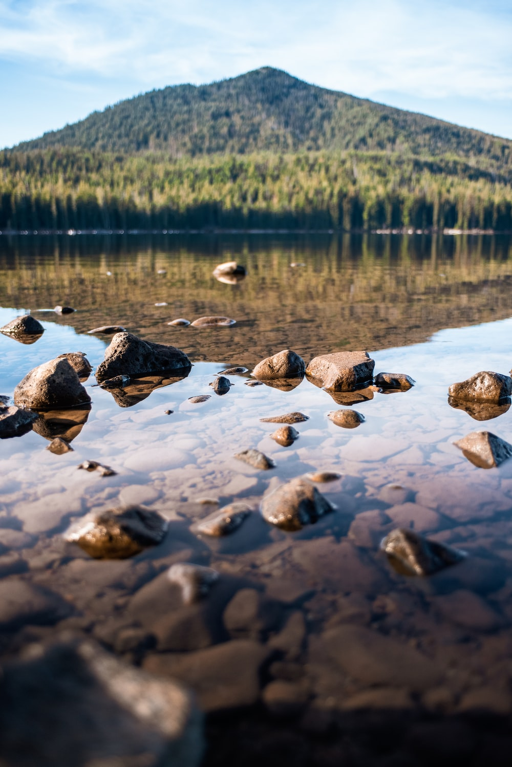 brown rocks on body of water viewing mountain under white and blue sky during daytime