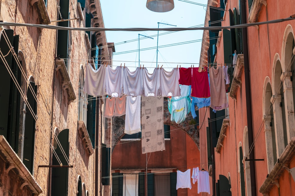several clothes on metal string between buildings