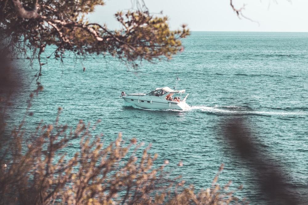 white motor boat sailing on body of water during daytime