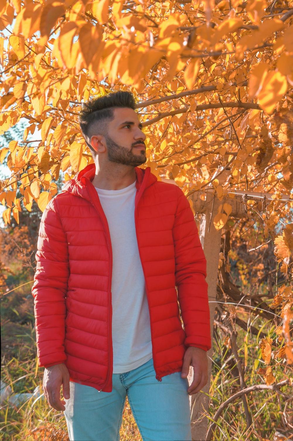 man wearing red zip-up bubble jacket under brown leaf tree