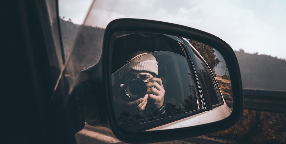 woman taking photo in front of vehicle side mirror