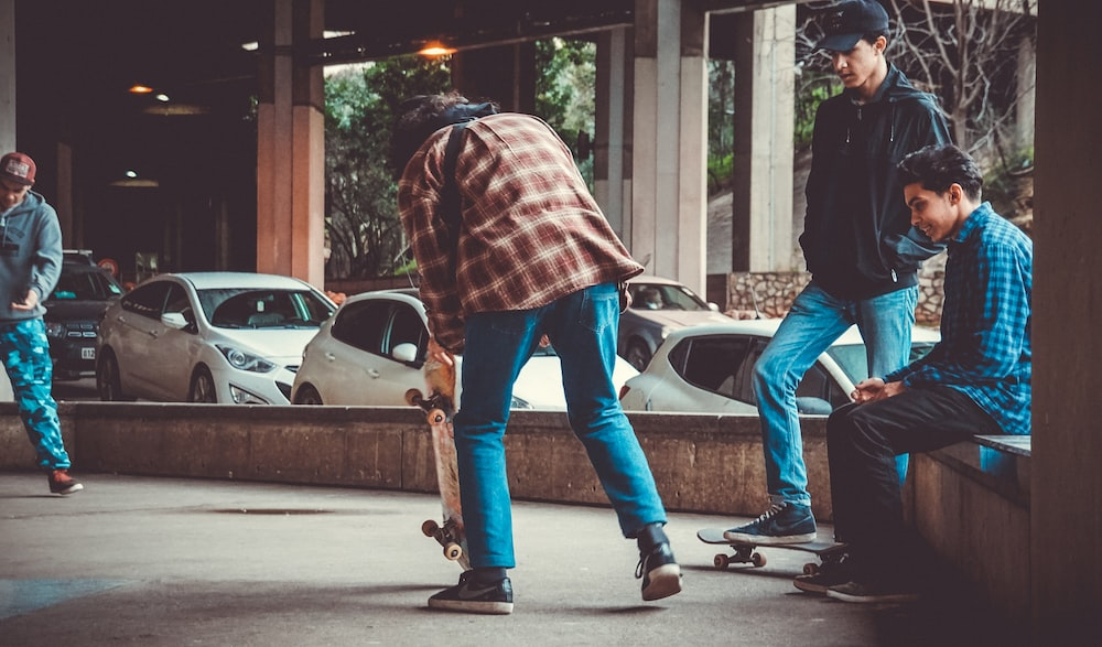 man holding skateboard while standing near another three men