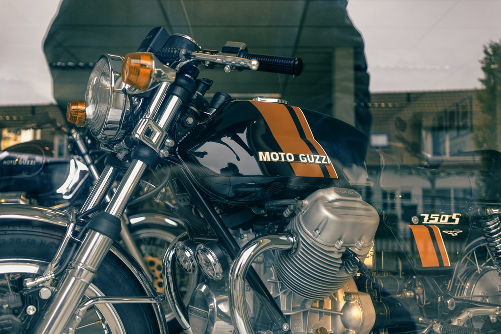 black and orange motorcycle parked in front of building