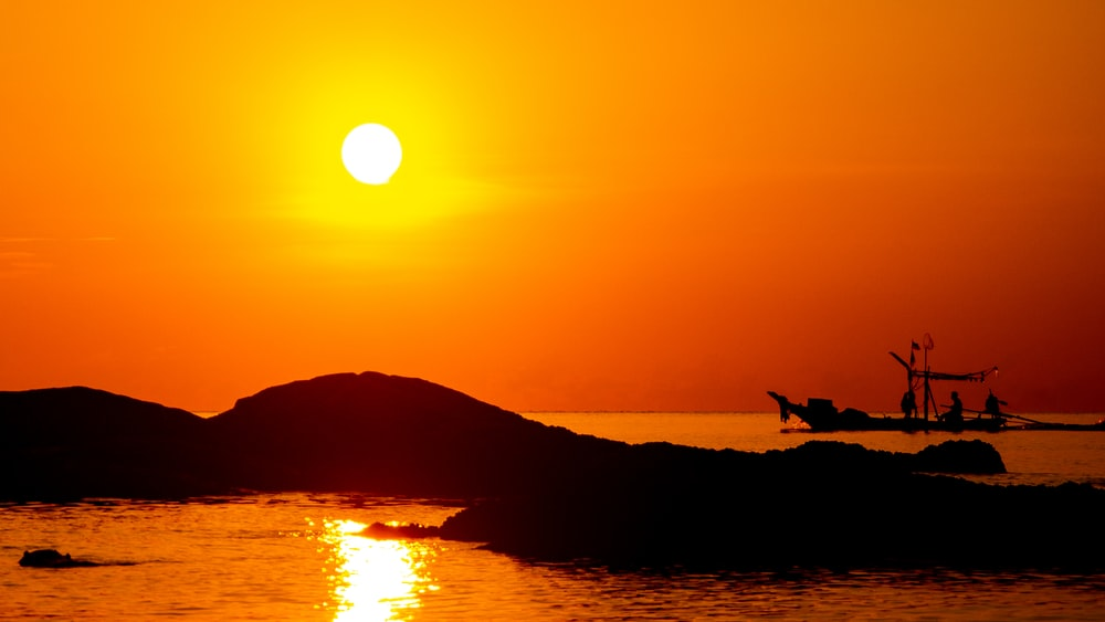 people in boat on body of water under orange sky