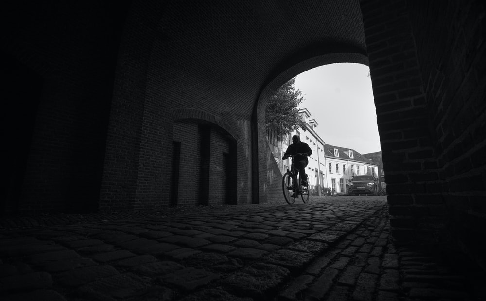 grayscale photography of man riding bicycle