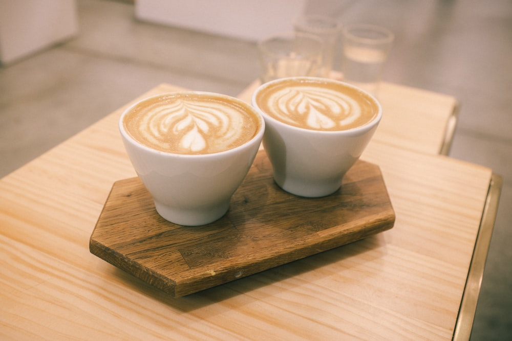 two white ceramic cups on board
