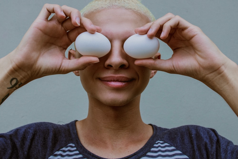 woman holding two white eggs