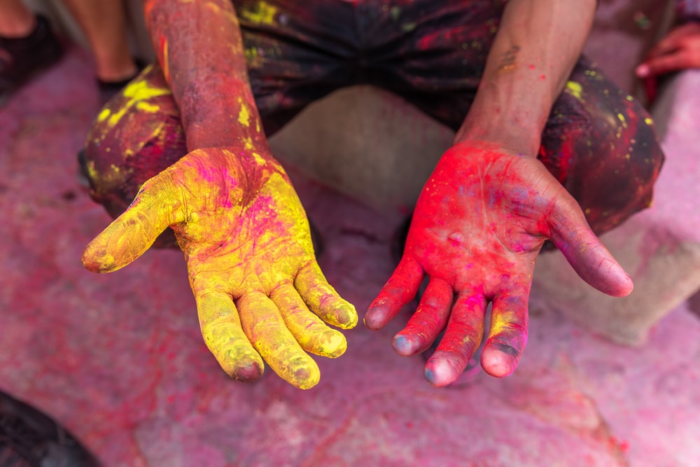 person's hand with yellow and red powder