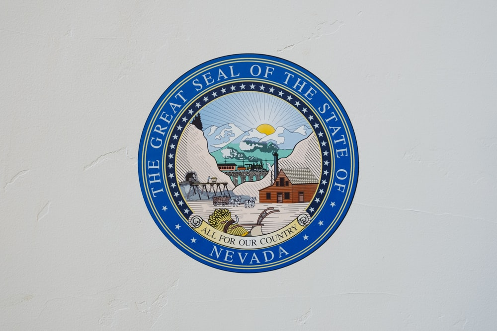 The Great Seal of the State of Nevada logo on white wall