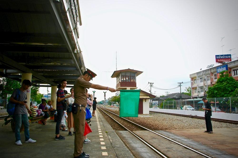 man standing beside railway