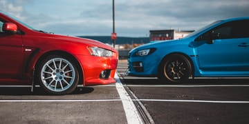 blue and red cars in parking lots