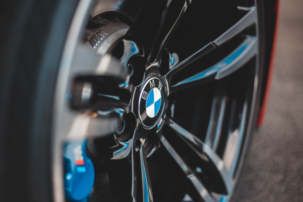 shallow focus photography of black and blue BMW car wheel
