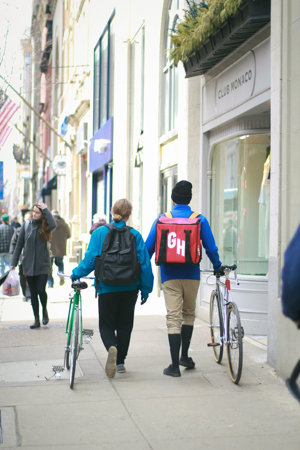 woman wearing blue pullover holding green city bike