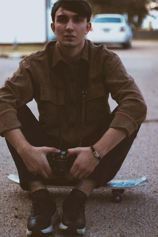 man sitting on skateboard deck