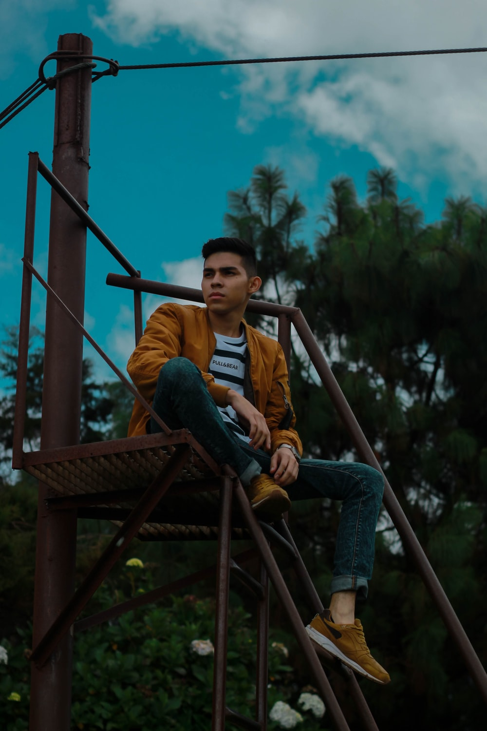 man in brown jacket and blue jeans sitting on brown steel stair outdoors