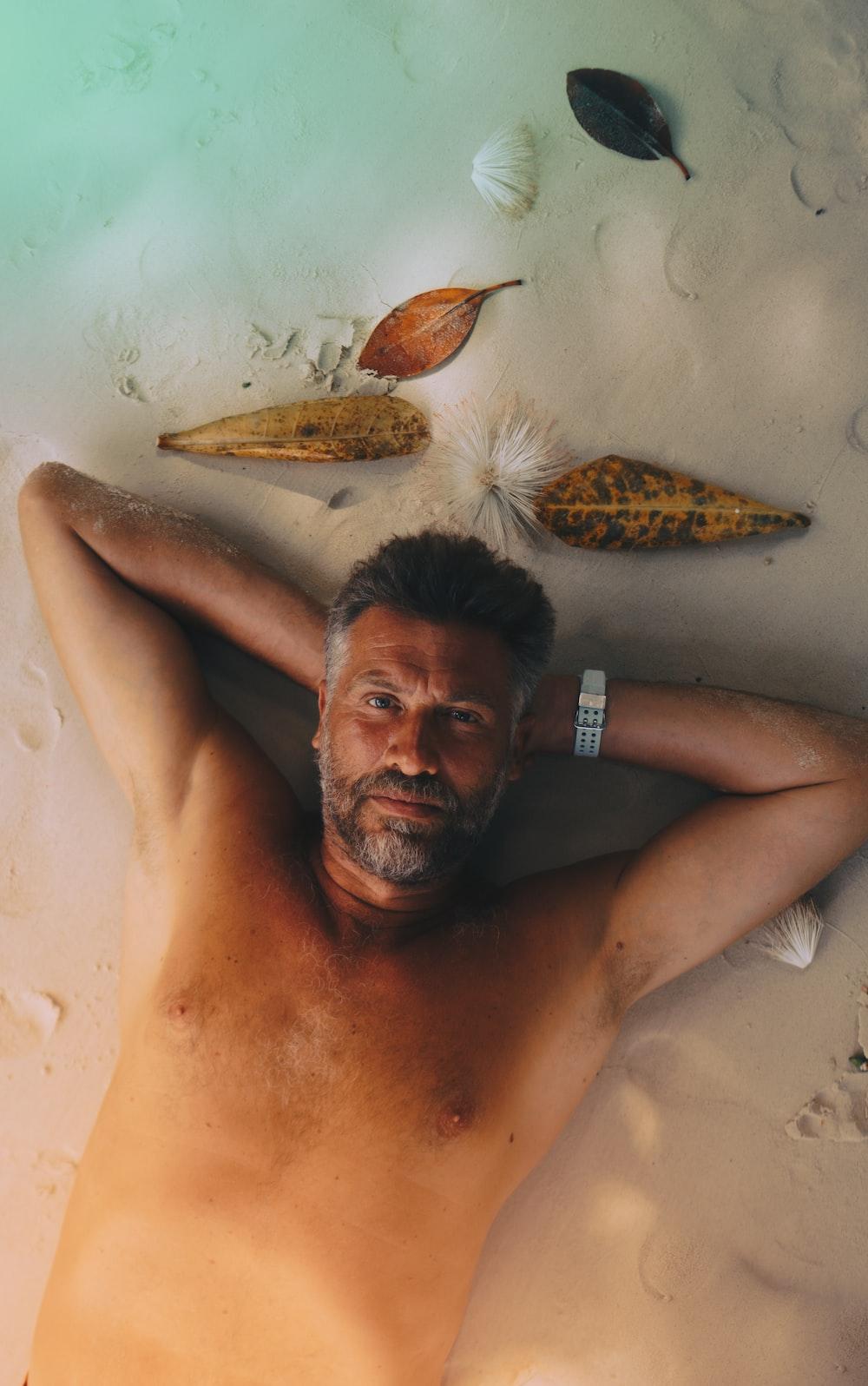 topless man lying on sand