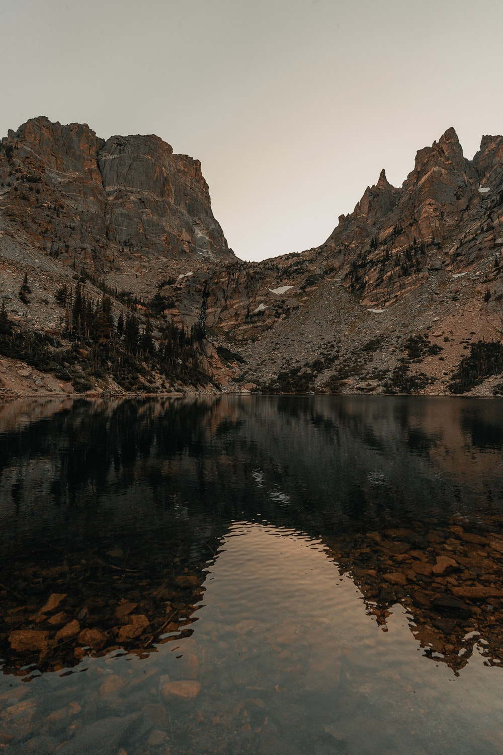 landscape photography of brown and black mountain ranges behind body of water