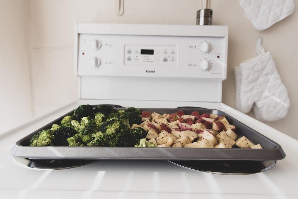 sliced broccoli on gray tray