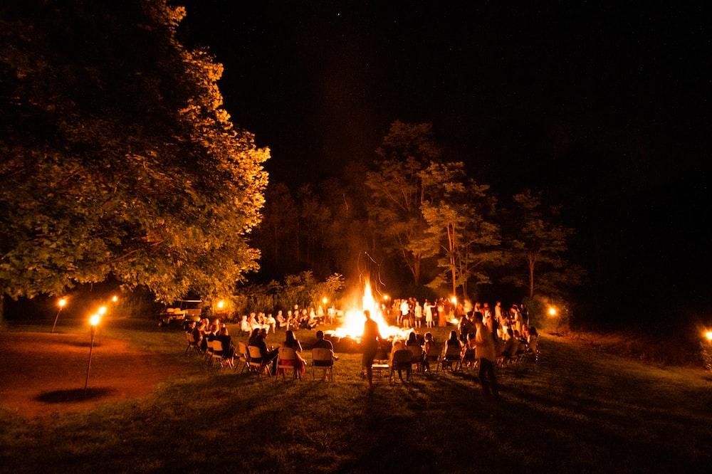 people sitting around bonfire