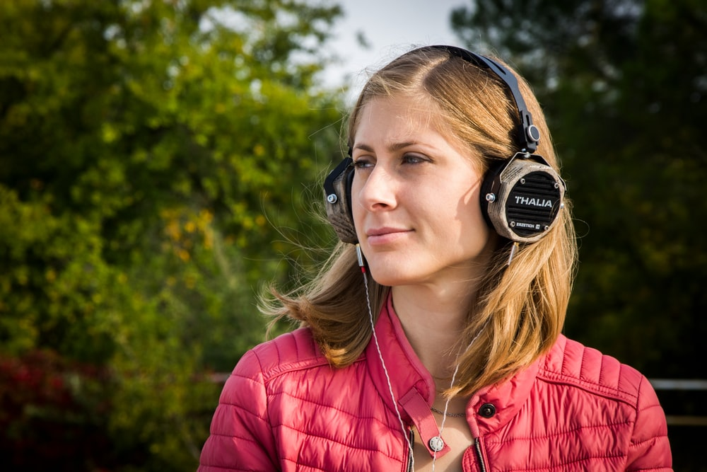 shallow focus photo of woman using black corded headphones