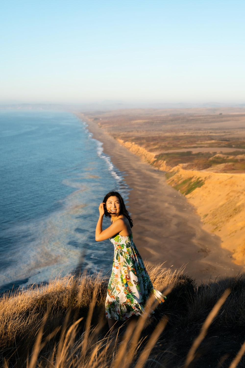 woman standing on mountain grass overviewing shoreline