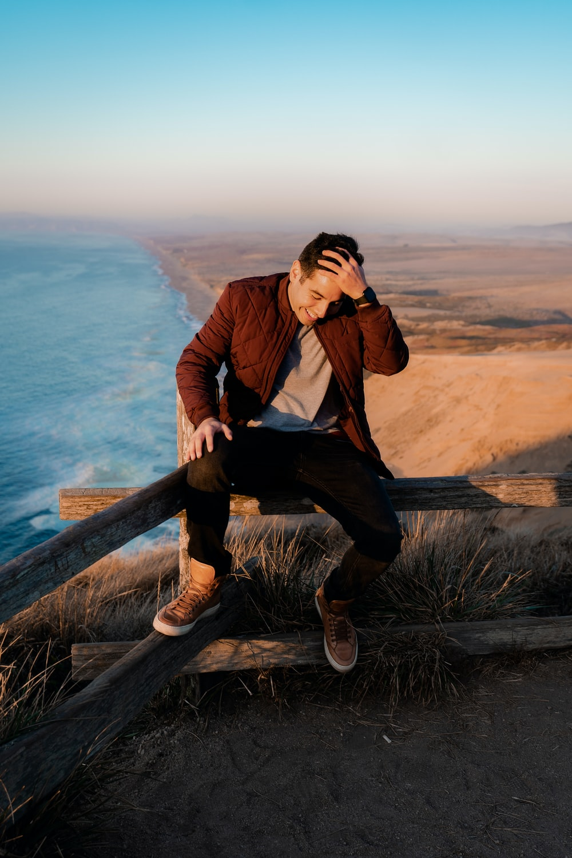 man wearing brown jacket sitting beside fence
