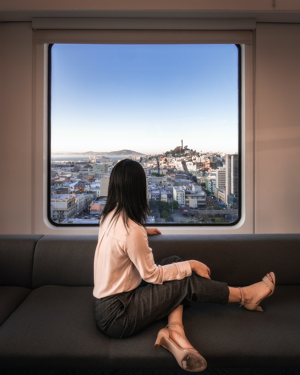 woman sitting on sofa near window