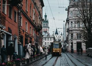 orange train on railroad beside people and buildings