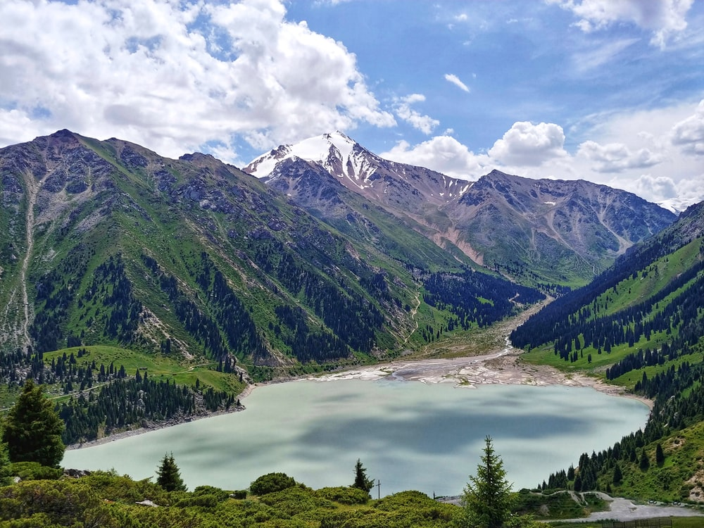 Big Almaty Lake under white and blue sky during daytime
