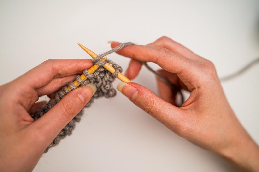 Woman knitting grey yarn