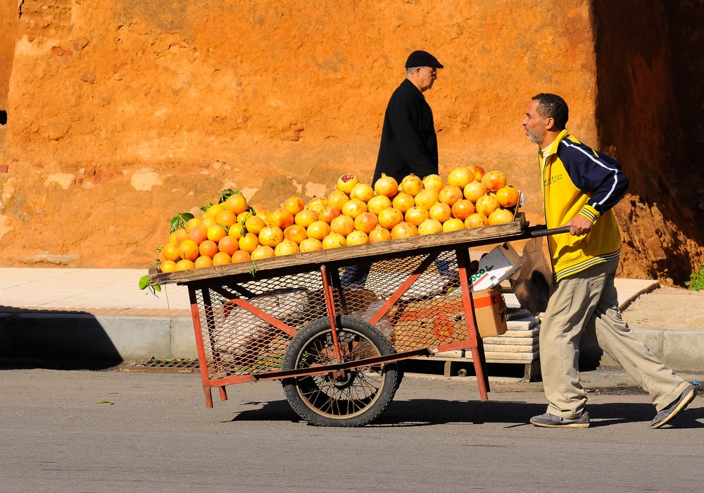 man pushing cart with oranges on top